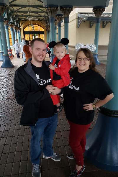 mom, dad, and son in matching disney shirts