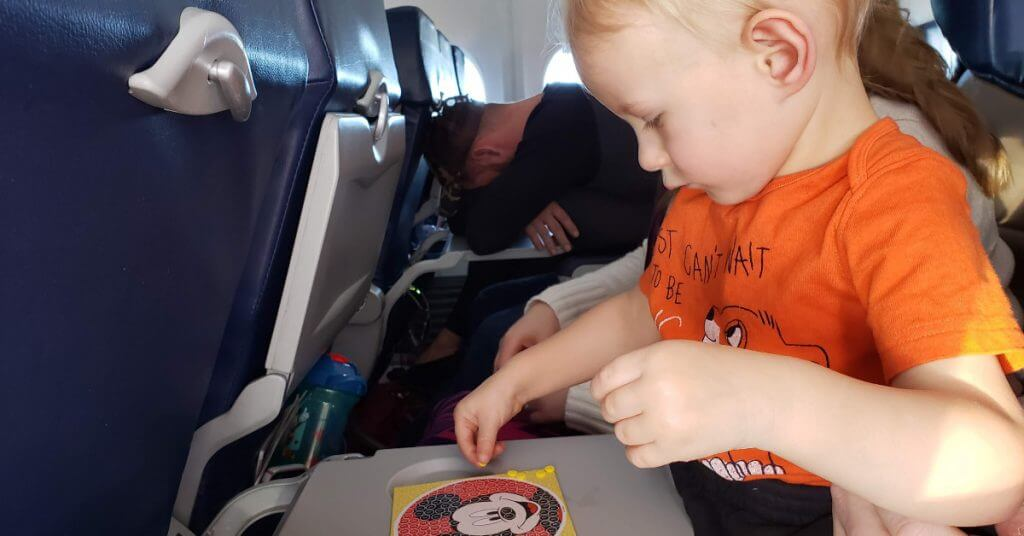 toddler Mini playing with Mickey sticker craft project on a plane