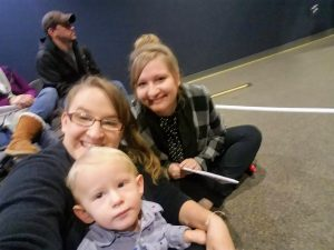 mom, aunt, and toddler sit on floor