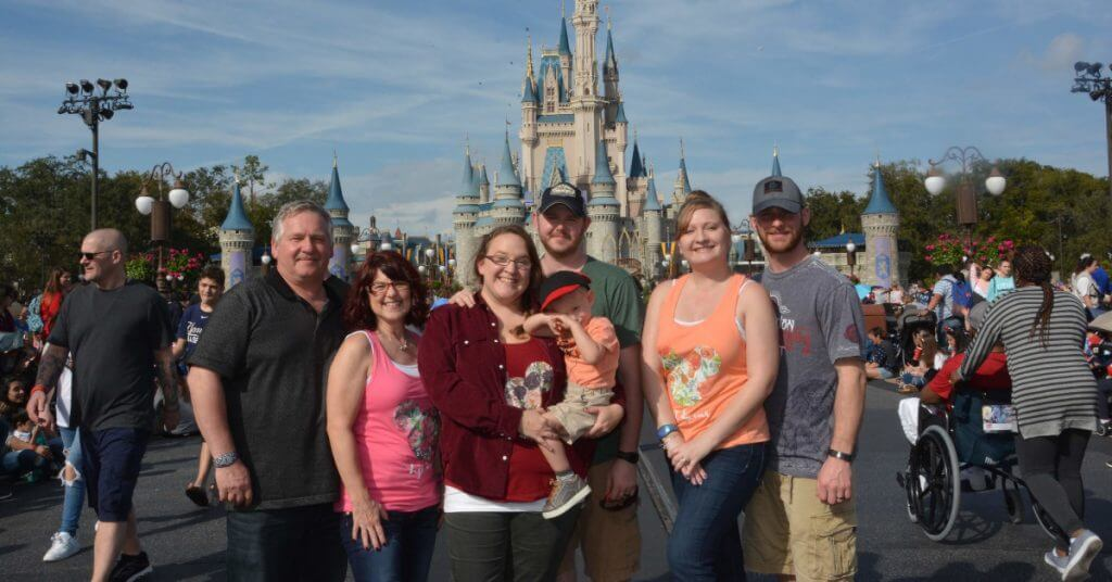 family photo in front of Cinderella's castle in Magic Kingdom at Walt Disney World