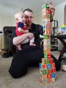 father and son building a block tower