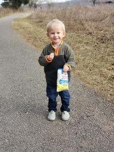 toddler walking outdoors carrying chips