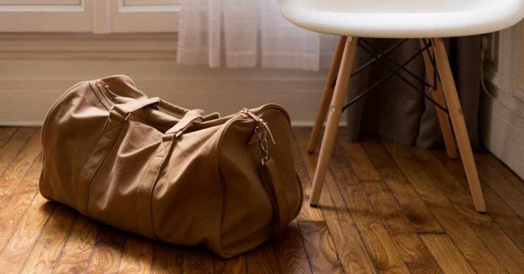 Duffel bag on floor next to chair