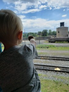 toddler looking out window at train