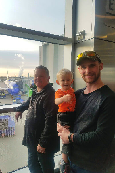 grandpa and uncle with toddler in an airport