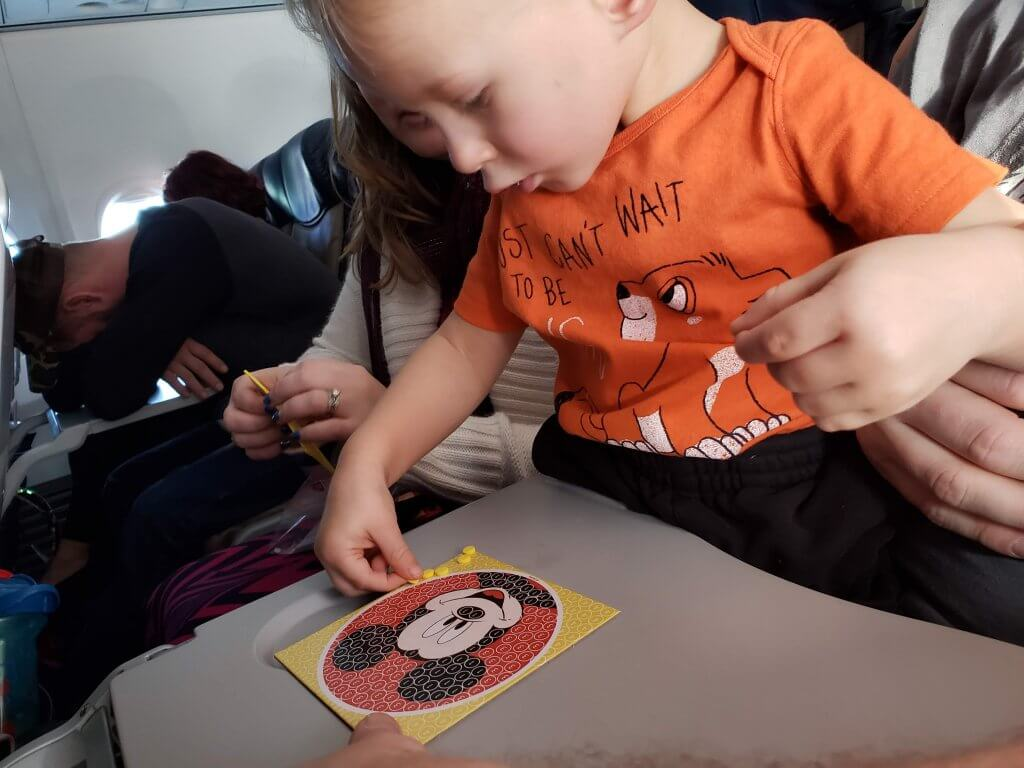 toddler playing with Mickey Mouse sticker craft on a plane, Exploration Motherhood