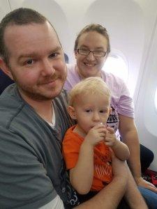 mom, dad, and toddler on plane explorationmotherhood.com